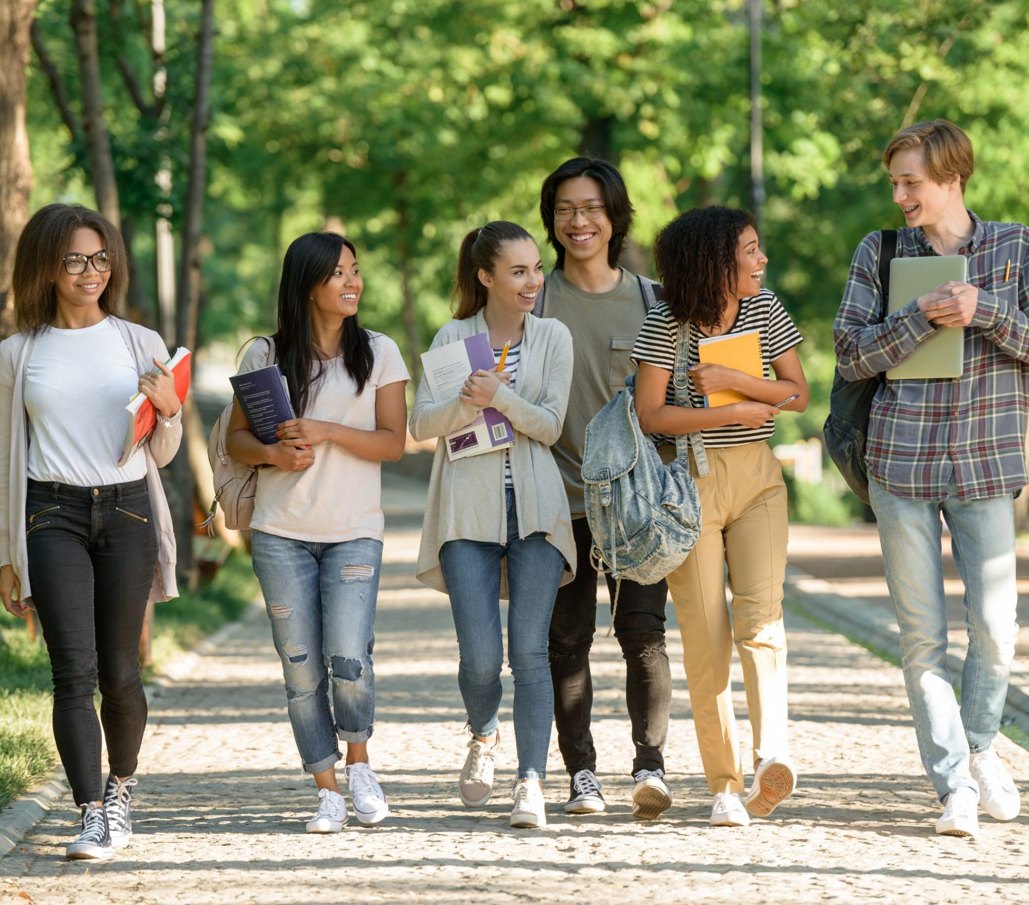 Picture of multiethnic group of young cheerful students walking while talking. Looking aside.
