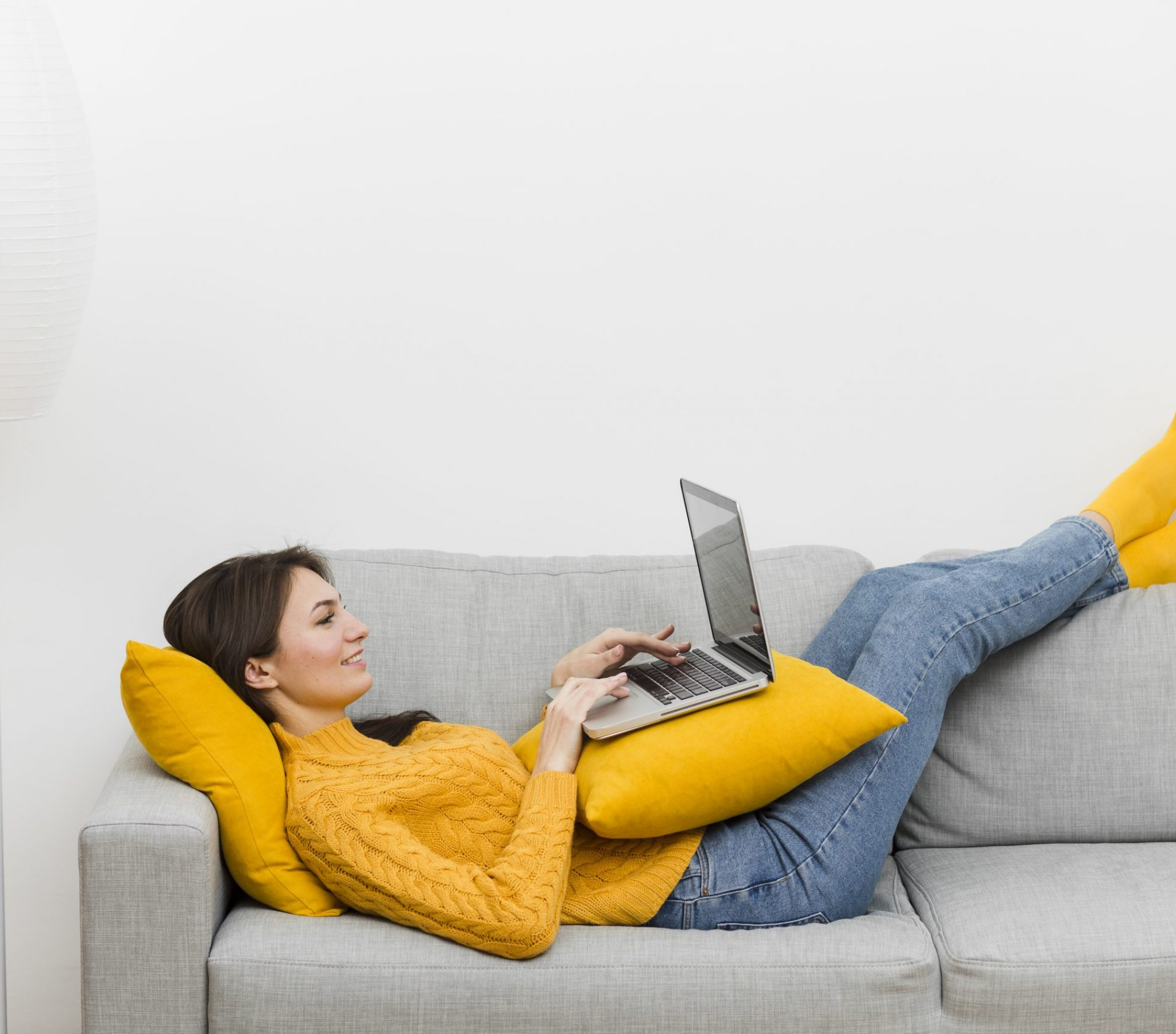 side-view-of-woman-relaxing-on-sofa-while-looking-at-laptop
